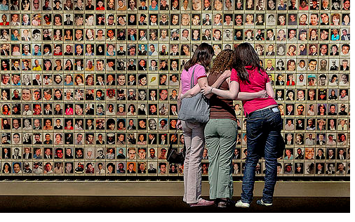 Visitors view the photo wall of fallen Americans at the 9-11 Memorial.