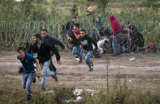 Syrian refugees run after entering Hungary from Serbia through a barbed wire fence, on the border near Roszke, Friday, Aug. 28, 2015. Hungary deployed police reinforcements to rein in an unrelenting flow of migrants across its porous border Thursday, but refugee activists said the effort appeared futile in a nation whose migrant camps are overloaded and barely delay their journeys west into the heart of the European Union. (AP Photo/Darko Bandic)