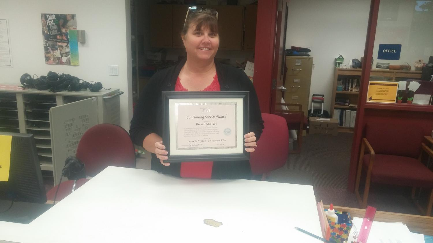 Doreen McCann holding up her 'Continuing Service Award'.