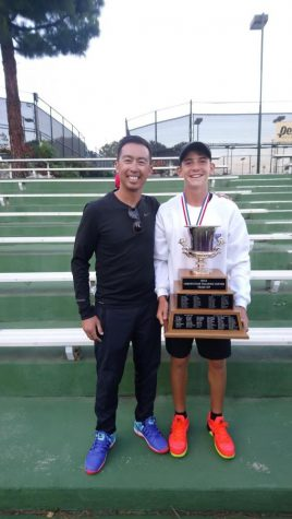 Martin is pictured here with one of his coaches, Coach Robert. Martin is holding a trophy that he had won from the California Tennis Competition (CTC). CTC has the highest level of tennis competition in a tournament in Southern California.