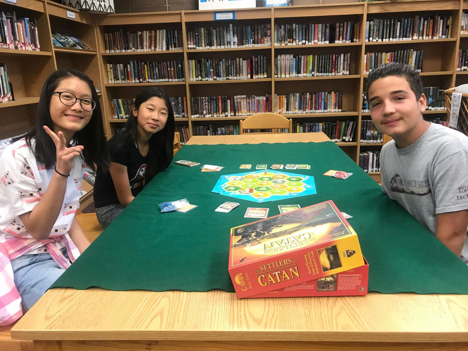 Hong Shui (Left), Kerry Wang (Far Left), and Farid Fred Sawaya (Right) are all enjoying a game of Catan.